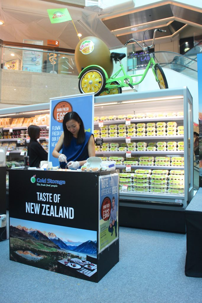 A merchant prepares her product for sampling at Cold Storage's New Zealand Food & Wine Fair
