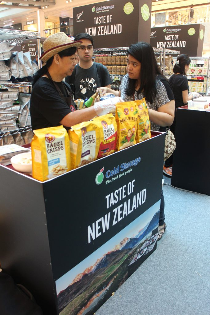 A shopper samples a snack at Cold Storage's New Zealand Food & Wine Fair, where more than 20 different products are available for sampling at from 23 - 29 May. This includes cheese, venison, wine and cider
